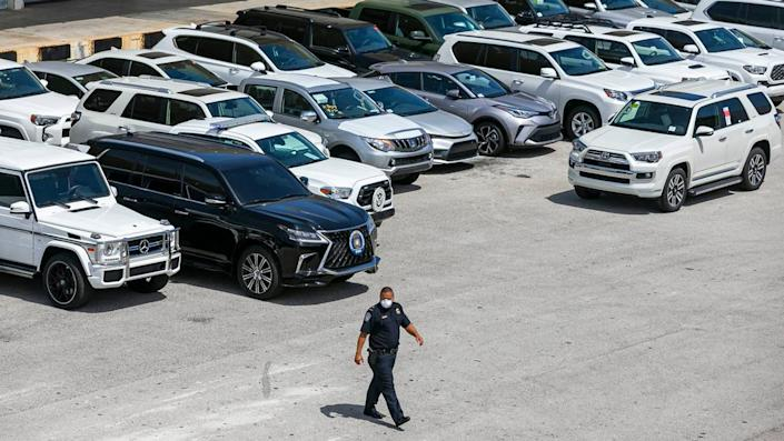 Dylan DeFrancisci, port director for U.S. Customs and Border Protection, walks past more than 80 vehicles seized by Homeland Security Investigations at Port Everglades on Tuesday, July 7, 2020. The vehicles, worth $3.2 million, were being shipped from Port Everglades to Venezuela. The cars, allegedly bought by a ring associated with the government of Venezuelan President Nicolas Maduro, were intercepted by Customs and Border Protection.