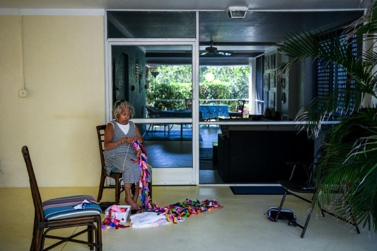 Cathy Tobias' friend Lucy Kancy, 69, ties ribbons on a string for the Covid-19 memorial project