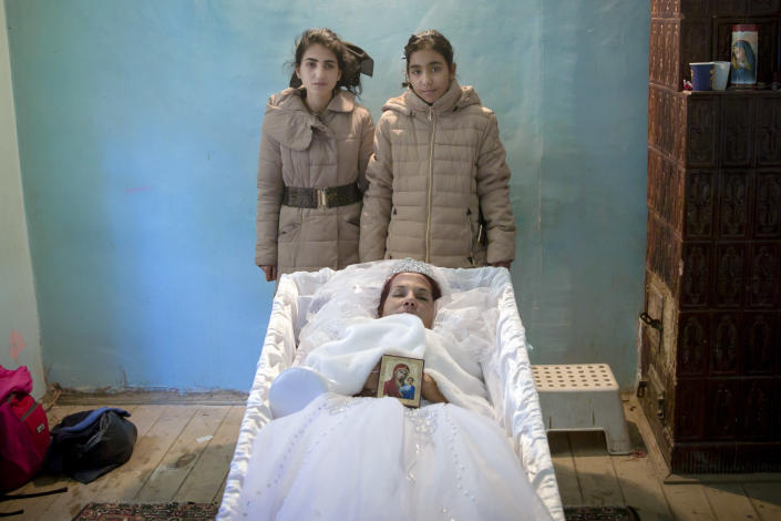 """FILE - In this Tuesday, Nov. 3, 2015 photograph, Maria Ion, a 38 year-old widow, mother of five, who died in last Friday's fire at the Colectiv nightclub where she occasionally worked as a cleaning lady, lies in a coffin wearing a bride dress as two of her children, Denisa, 15 years-old, left, and 11 year-old Alexandra pose next to it, at the family house in Bucharest, Romania. The Oscar-nominated Romanian documentary film """"Collective"""" follows a group of journalists delving into the state of health care in the eastern European country in the wake of a deadly 2015 nightclub fire that left dozens of burned victims in need of complex treatment. What they revealed was decades of deep-rooted corruption, a heavily politicized system scarily lacking in care. (AP Photo/Vadim Ghirda, File)"""