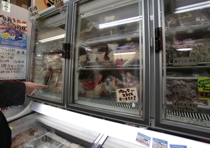 A shopper points at packed whale meat in a freezer at a whale meat specialty store at Tokyo's Ameyoko shopping district, Thursday, March 27, 2014. The greatest threat to Japan's whaling industry may not be the environmentalists harassing its ships or the countries demanding its abolishment, but Japanese consumers. They've simply lost their appetite. The amount of whale meat stockpiled for lack of buyers has nearly doubled over 10 years, even as anti-whaling protests helped drive catches to record lows. More than 2,300 mink whales worth of meat is sitting in freezers while whalers still plan to catch another 1,300 whales per year. Uncertainty looms ahead of an International Court of Justice ruling expected Monday over a 2010 suit filed by Australia, which argues that Japan's whaling - ostensibly for research - is a cover for commercial hunts. (AP Photo/Shizuo Kambayashi)