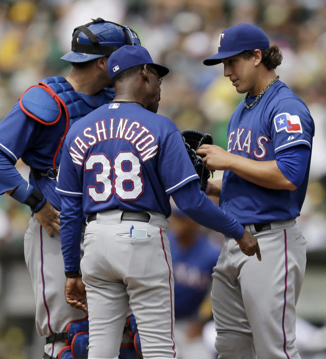 Texas Rangers manager Ron Washington (38) talks with pitcher Derek Holland in the fourth inning of a baseball game against the Oakland Athletics, Monday, Sept. 2, 2013, in Oakland, Calif. (AP Photo/Ben Margot)