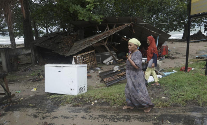 Residents walk past a house damaged by a tsunami, in Carita, Indonesia, Sunday, Dec. 23, 2018. The tsunami apparently caused by the eruption of an island volcano killed a number of people around Indonesia's Sunda Strait, sending a wall of water crashing some 65 feet (20 meters) inland and sweeping away hundreds of houses including hotels, the government and witnesses said. (AP Photo/Dian Triyuli Handoko)