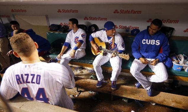 Chicago Cub backup catcher John Baker, center, plays his guitar during a rain delay at Wrigley Field during the fifth inning of a baseball game between the San Francisco Giants and the Chicago Cubs on Tuesday, Aug. 19, 2014, in Chicago. (AP Photo/Jeff Haynes)