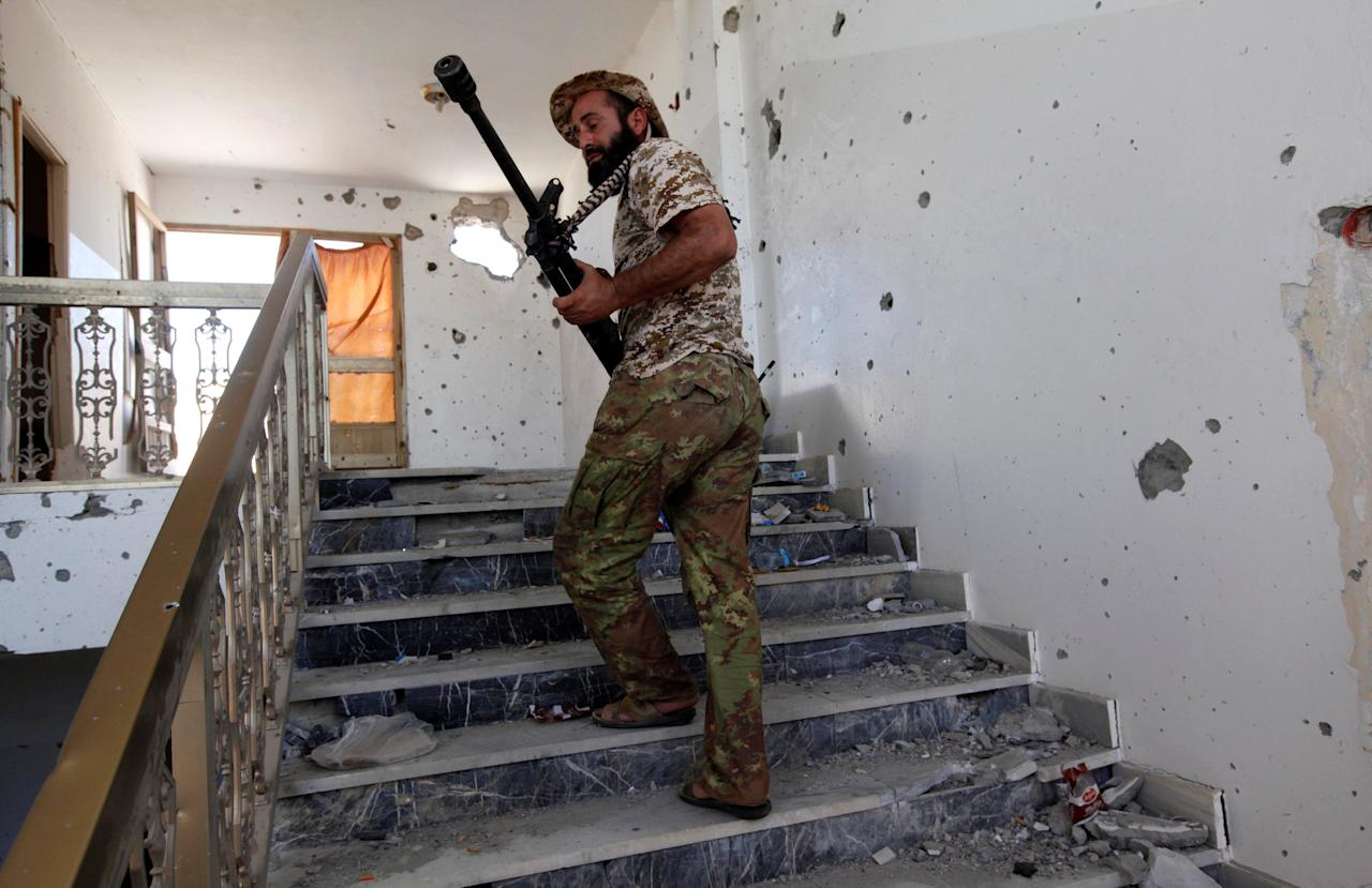 A fighter from Libyan forces allied with the U.N.-backed government walks up the stairs of a building during a battle with Islamic State militants in Sirte, Libya September 24, 2016. REUTERS/Ismail Zitouny