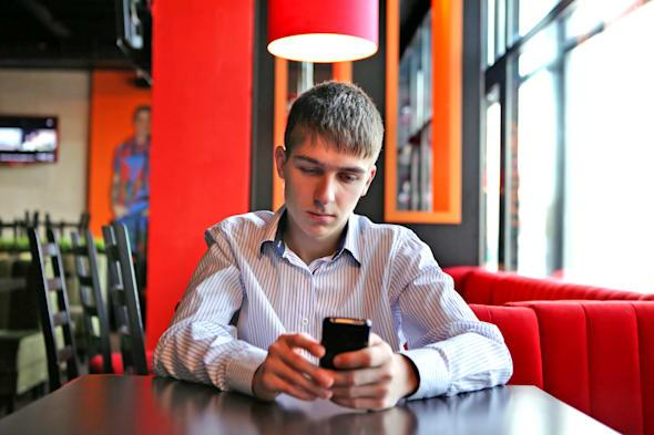 Sad Young Man with Mobile Phone at the table