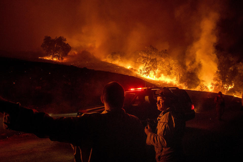 Firefighters confer while battling the Kincade Fire near Geyserville, Calif., on Thursday, Oct. 24, 2019. Portions of Northern California remain in the dark after Pacific Gas & Electric cut power to prevent wildfires from sparking during dry and windy conditions. (Photo: Noah Berger/AP)