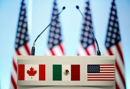 FILE PHOTO: The flags of Canada Mexico and the U.S. are seen on a lectern before a joint news conference on the closing of the seventh round of NAFTA talks in Mexico City