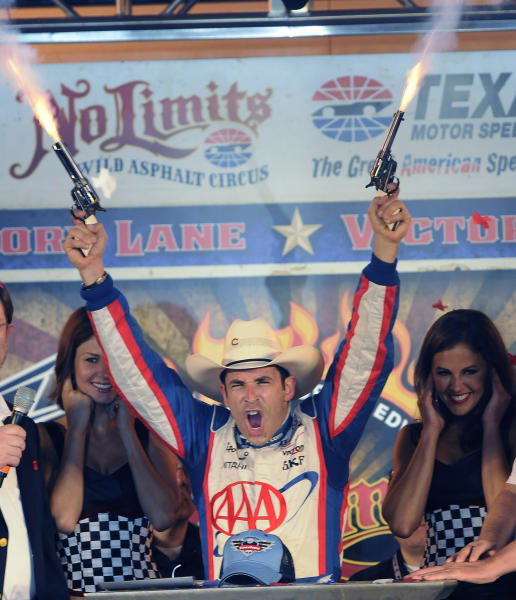 Helio Castroneves, of Brazil, guns loaded with blanks after he won the IndyCar auto race Saturday, June 8, 2013, at Texas Motor Speedway in Fort Worth, Texas. (AP Photo/Larry Papke)