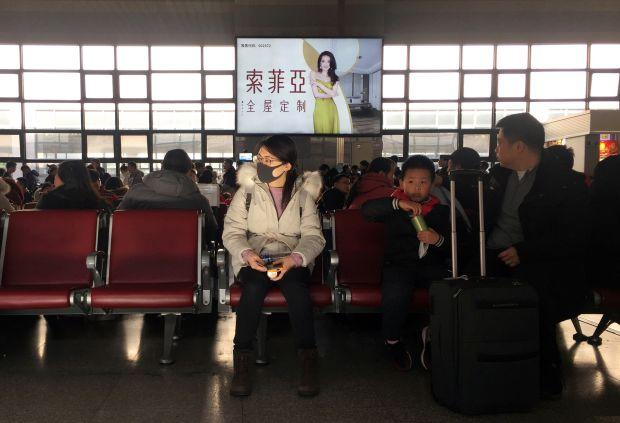 A woman wearing a mask is seen at a waiting area for a train to Wuhan at the Beijing West Railway Station