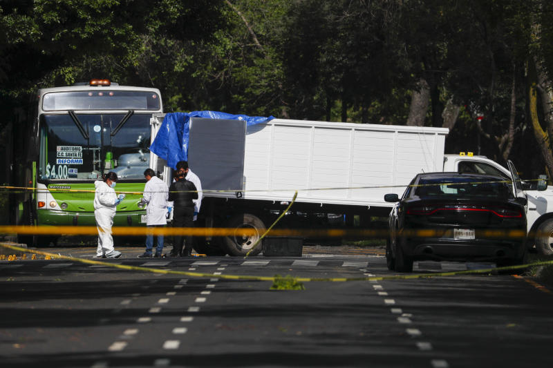 Forensic investigators and police work next to an abandoned white truck believed to have been used by gunmen at the scene where security secretary, Omar García Harfuch, was attacked in Mexico City, Friday, June 26, 2020. Heavily armed gunmen attacked and wounded Mexico City's police chief in an operation that left an unspecified number of dead. (AP Photo/Rebecca Blackwell)