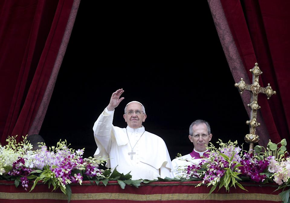 """Pope Francis waves as he delivers a """"Urbi et Orbi"""" message from the balcony overlooking St. Peter's Square at the Vatican April 5, 2015. REUTERS/Alessandro Bianchi"""