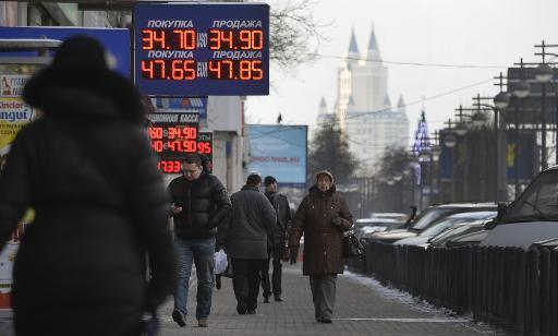 People walk under a chain of currency exchange offices in central Moscow on January 27, 2014