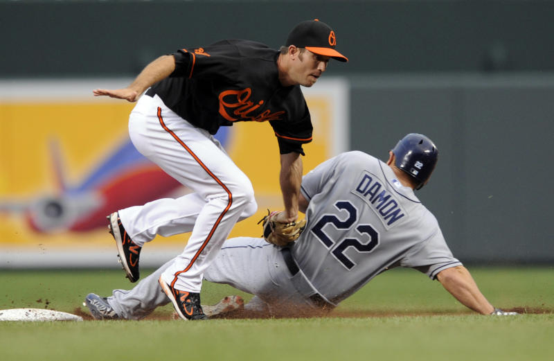 Baltimore Orioles shortstop J.J. Hardy, left, tags out Tampa Bay Rays' Johnny Damon on a steal-attempt  in the first inning of a baseball game on Friday, June 10, 2011, in Baltimore. (AP Photo/Gail Burton)