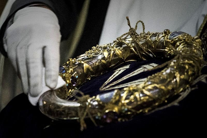 A priest seen wiping the Crown of Thorns, a relic believers say is from the crucifixion of Christ, and one of the most famous items saved at  Notre-Dame