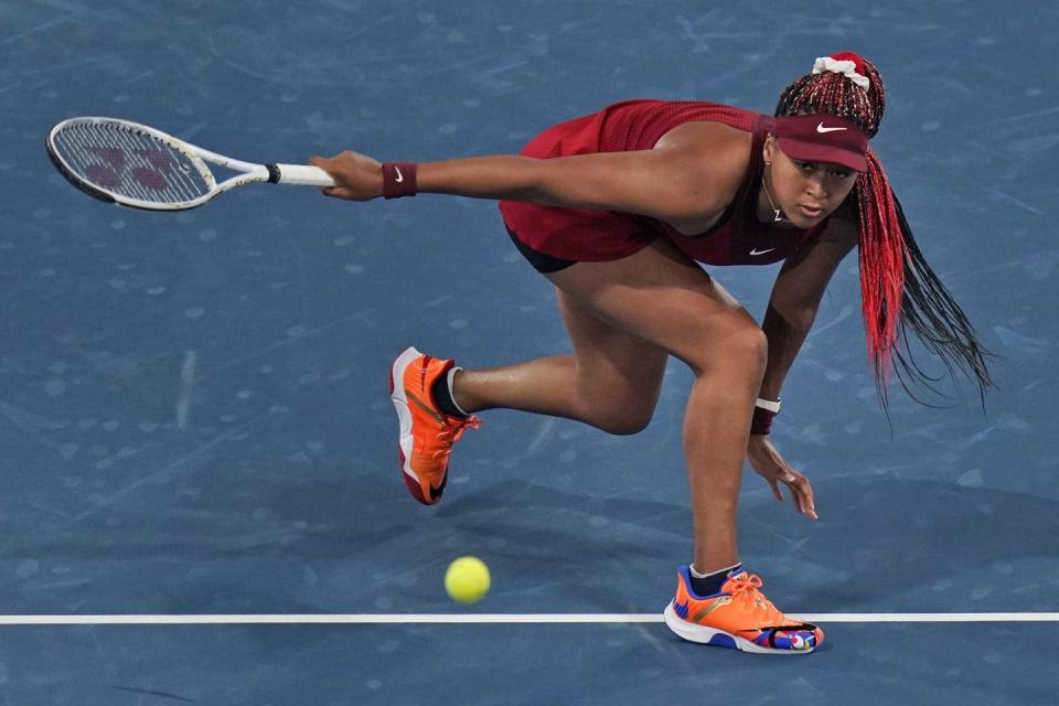 Woman player crouched with a tennis racquet in one hand after returning a hit.
