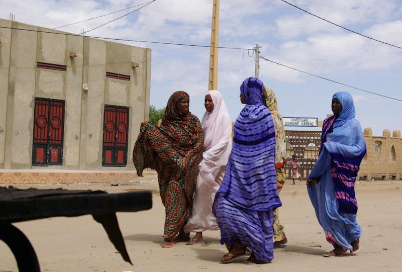 FILE - In this Oct. 18, 2012 file photo, women wearing veils as mandated by Islamist group Ansar Dine, walk along a street in Timbuktu, Mali. The Mali army attacked Islamist rebels with heavy weapons in the center of the country which divides the insurgent-held north and the government-controlled south, government officials said Thursday, Jan. 10, 2013. (AP Photo/File)