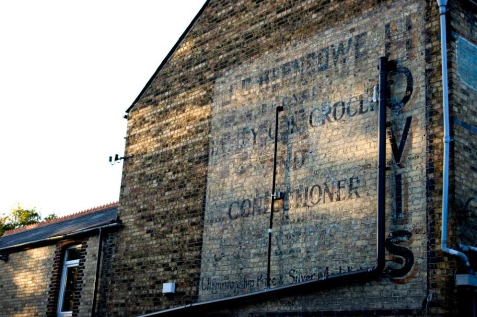 The sign for an old grocery store is still visible on the wall of this building in Oxford