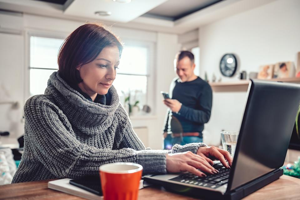 Woman wearing grey sweater using laptop at home office while her husband using smart phone in the background