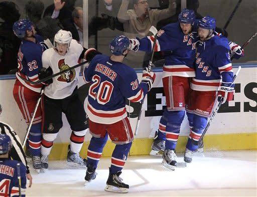 Members of the New York Rangers celebrate a goal by Marc Staal, second from right, as Ottawa Senators' Kyle Turris, second from left, gets caught in the celebration during the second period of Game 7 of a first-round NHL hockey Stanley Cup playoff series on Thursday, April 26, 2012, in New York. (AP Photo/Julio Cortez)