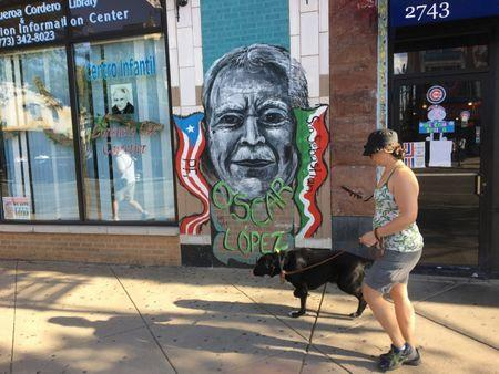 A woman passes a street mural of Oscar Lopez Rivera in Chicago