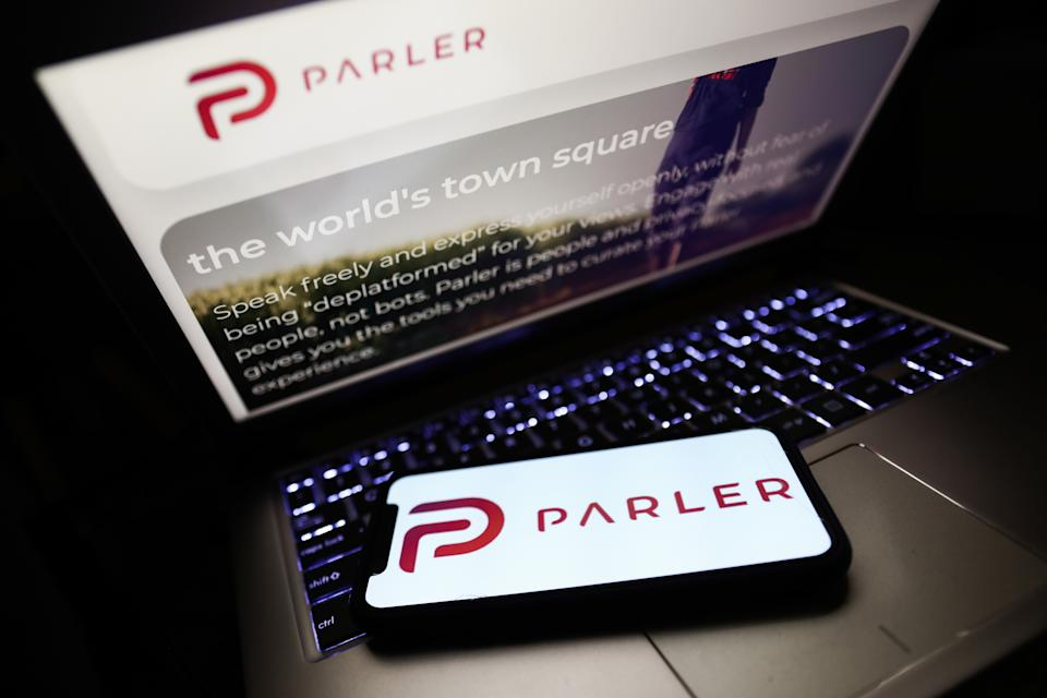 Parler app logo displayed on a phone screen and Parler website displayed on a laptop screen are seen in this illustration photo taken in Poland on January 10, 2020. Tech giants Google, Apple and Amazon have blocked the Parler app from their platforms, as a dangerous for the public safety.  (Photo illustration by Jakub Porzycki/NurPhoto via Getty Images)