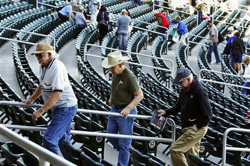 Fans leave the stadium as a fire alarm goes off in the eighth inning of an exhibition spring training baseball game between the Seattle Mariners and the Cleveland Indians, Wednesday, Feb. 27, 2013, in Goodyear, Ariz. The game eventually resumed, and the Mariners won 5-1. (AP Photo/Ross D. Franklin)