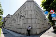 FILE PHOTO: A man looks at a mobile phone in front of the Bank of Japan building in Tokyo