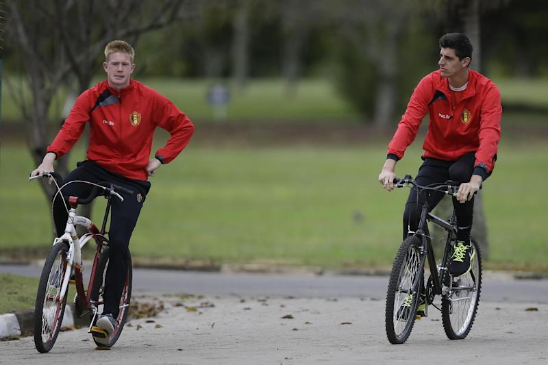 Belgium's Kevin De Bruyne, left, and goalkeeper Thibaut Courtois ride bicycles as they arrive at a training session of Belgium in Mogi Das Cruzes, Brazil, Thursday, June 19, 2014. Belgium play in group H of the 2014 soccer World Cup