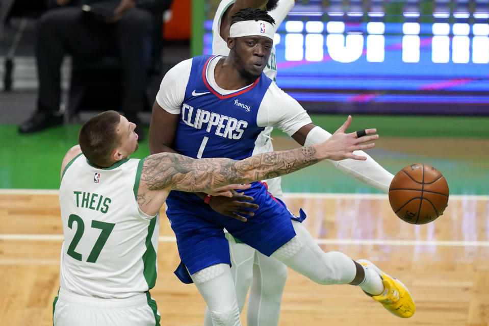 LA Clippers guard Reggie Jackson (1) passes the ball against the defense of Boston Celtics center Daniel Theis (27) in the first quarter of an NBA basketball game, Tuesday, March 2, 2021, in Boston. (AP Photo/Elise Amendola)
