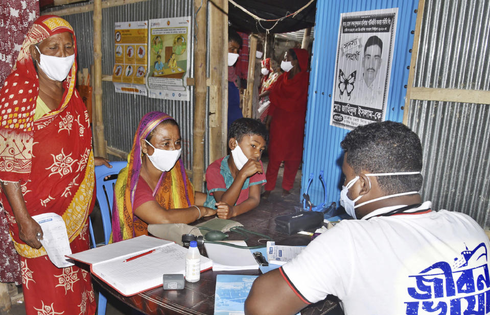 In this photo provided by Bidyanondo Foundation, a doctor writes a prescription for a patient after arriving at Banishanta village near Mongla seaport in southwestern region of Bangladesh, Sept. 1, 2020. A Bangladeshi charity has set up a floating hospital turning a small tourist boat into a healthcare facility to provide services to thousands of people affected by this year's devastating floods that marooned millions. (Bidyanondo Foundation via AP)