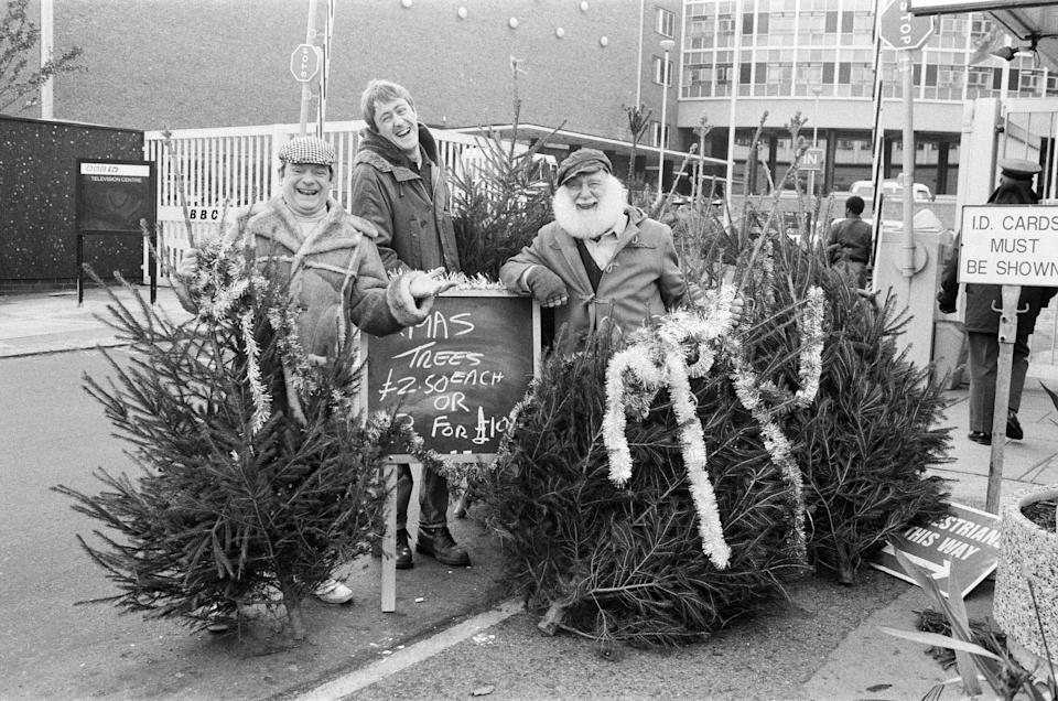 Left to right, David Jason as Del Boy, Nicholas Lyndhurst as Rodney and Buster Merryfield as Uncle Albert from 'Only Fools and Horses ' with Christmas trees outside the BBC Television Centre, 7th December 1987. (Photo by Stone/Daily Mirror/Mirrorpix/Getty Images)
