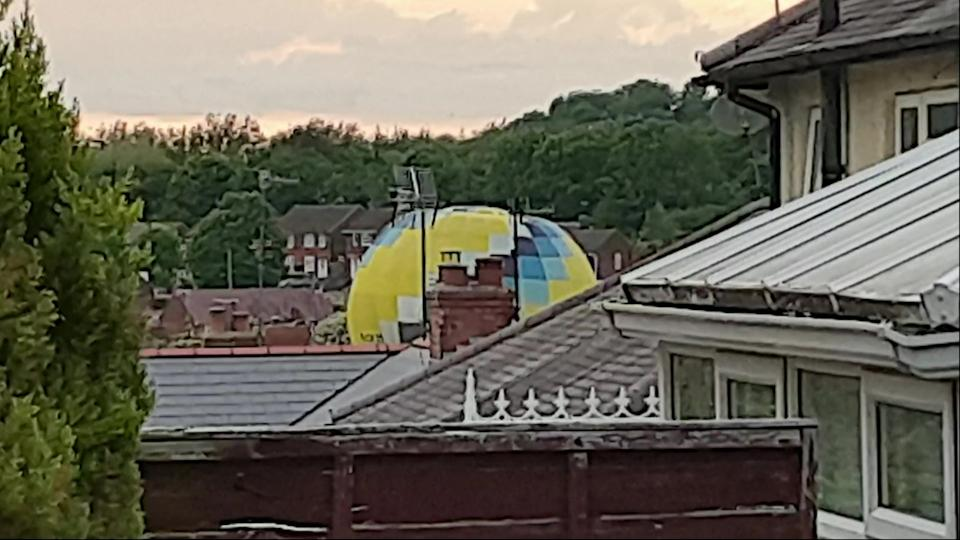 Video grab of  the moment a hot air balloon accidentally landed in a residential housing estate. (SWNS)