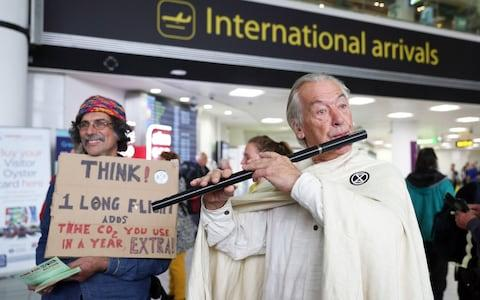 A flautist joins protesters in the South Terminal - Credit: PA