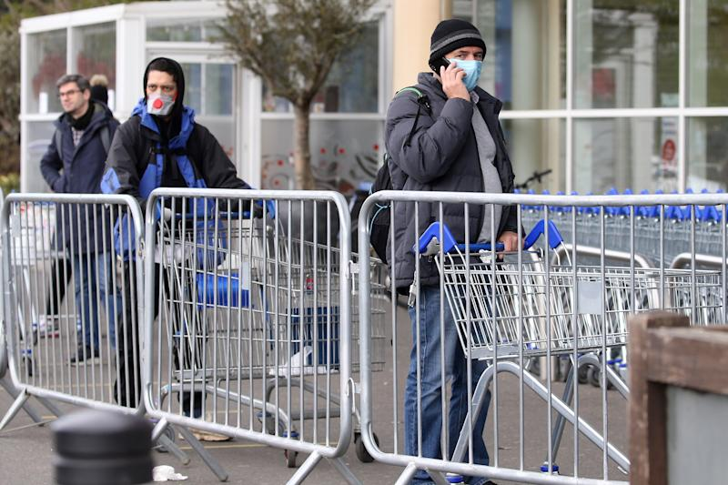A shopper wears a mask as he stands with a shopping trolley behind metal barriers, whilst waiting to enter a Tesco supermarket that is limiting customers entering, in north-west London on March 31, 2020, as life in Britain continues during the nationwide lockdown to combat the novel coronavirus pandemic. - The novel coronavirus pandemic has so far claimed nearly 38,000 lives worldwide in a health crisis that is rapidly reorganising political power, hammering the global economy and the daily existence of some 3.6 billion people. (Photo by ISABEL INFANTES / AFP) (Photo by ISABEL INFANTES/AFP via Getty Images)