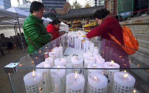 Women place candles for the success of their relatives sitting the annual College Scholastic Ability Test, at the Jogye Buddhist temple in Seoul on November 23, 2017 - Credit:  AFP