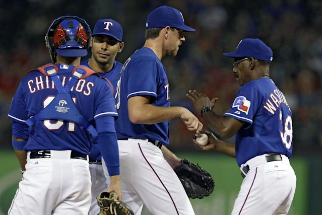 Texas Rangers catcher Robinson Chirinos and Carlos Pena, left rear, watch as starting pitcher Nick Tepesch turns the ball over to manager Ron Washington in the seventh inning of a baseball game against the Los Angeles Angels, Friday, July 11, 2014, in Arlington, Texas. (AP Photo/Tony Gutierrez)