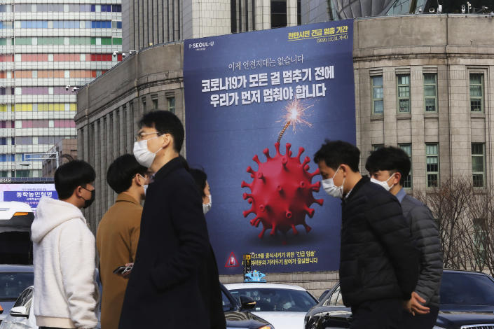 """A banner emphasizing an enhanced social distancing campaign is displayed on the wall of Seoul City Hall in Seoul, South Korea, Wednesday, Nov. 25, 2020. The banner reads: """"We have to stop before COVID-19 stops everything."""" (AP Photo/Ahn Young-joon)"""