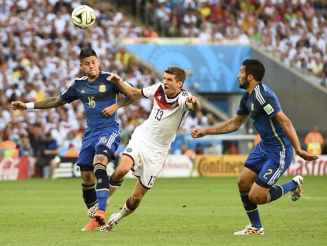 Germany's Thomas Mueller (C) fights for the ball with Argentina's Marcos Rojo and Ezequiel Garay (R) during their 2014 World Cup final at the Maracana stadium in Rio de Janeiro July 13, 2014. REUTERS/Dylan Martinez (BRAZIL - Tags: SOCCER SPORT WORLD CUP)
