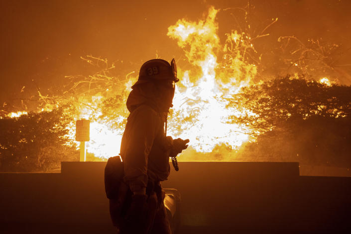 In this Thursday, Oct. 10, 2019 photo, a firefighter monitors the Saddleridge fire near homes in Sylmar, Calif. (Photo: Michael Owen Baker/AP)