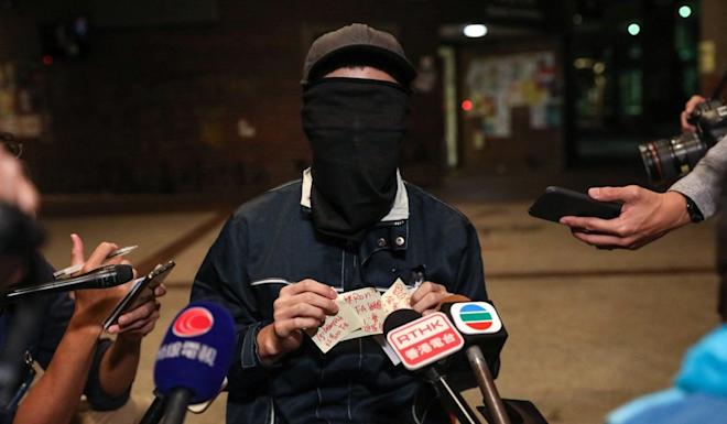 A masked radical speaks to the media at the PolyU campus at about 4.10am on Tuesday. Photo: Dickson Lee