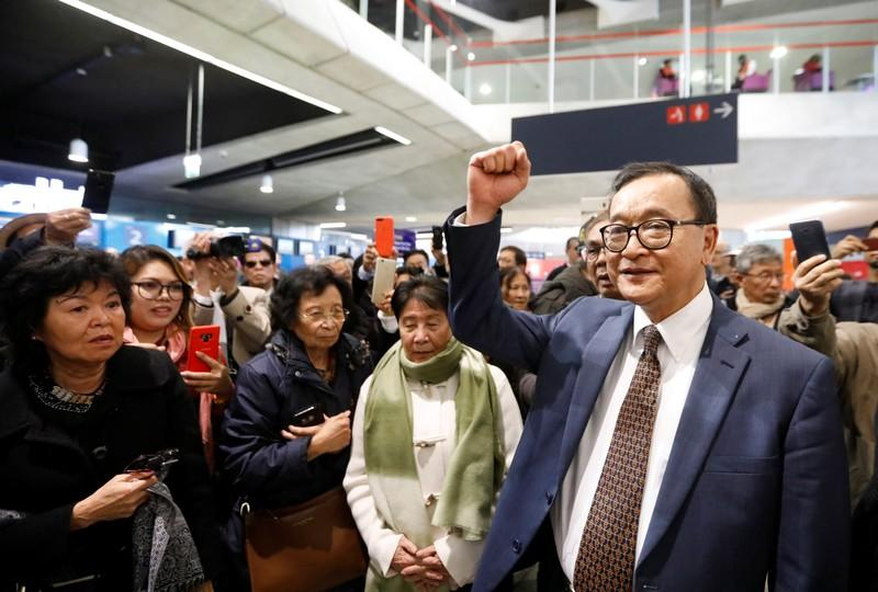 Cambodia's self-exiled opposition party founder Sam Rainsy, who has vowed to return to his home country, gestures to supporters after being prevented from checking-in for a flight from Paris to Bangkok at Roissy Airport in Paris