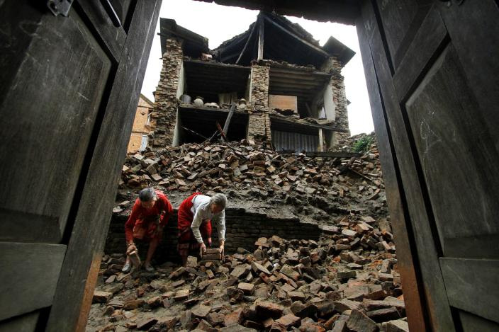 Nepalese women remove bricks of the damaged house to make way for pedestrians after an earthquake of magnitude 6.9 shook northeastern India on Sunday night, in Katmandu, Nepal, Monday, Sept. 19, 2011. Rescue workers used shovels and their bare hands to pull bodies from the debris of collapsed buildings Monday, as the death toll from an earthquake that hit northeast India, Nepal and Tibet rises.