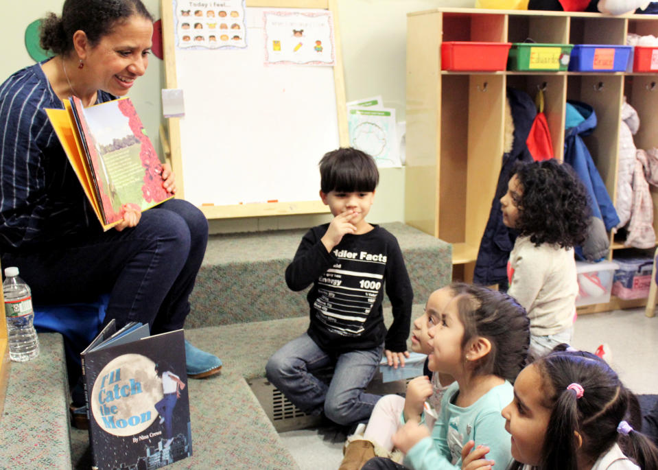 """In this 2018 photo provided by Children's Aid, Nina Crews, illustrator of """"A Girl Like Me,"""" reads to children at an early childhood education center. Crews said the work of independent publishers and grassroots organizers are vital in bringing more diversity into children's books. (Adriana Alba/Children's Aid via AP)"""