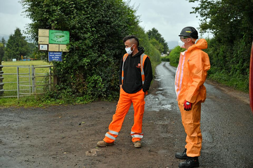 Contractors in PPE, waiting to go onsite, outside Rook Row Farm in Mathon, near Malvern, Herefordshire, where there have been 73 positive cases of coronavirus confirmed.