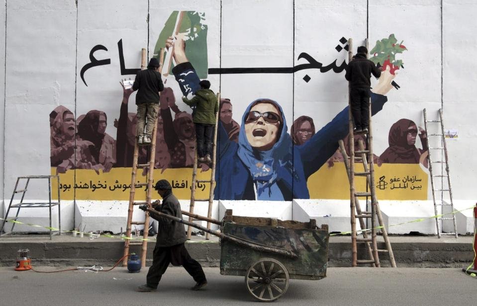 """<span class=""""caption"""">In this March 2019 photo, Afghan artists work on a barrier wall of the Ministry of Women's Affairs marking International Women's Day, in Kabul, Afghanistan.</span> <span class=""""attribution""""><span class=""""source"""">(AP Photo/Rahmat Gul)</span></span>"""