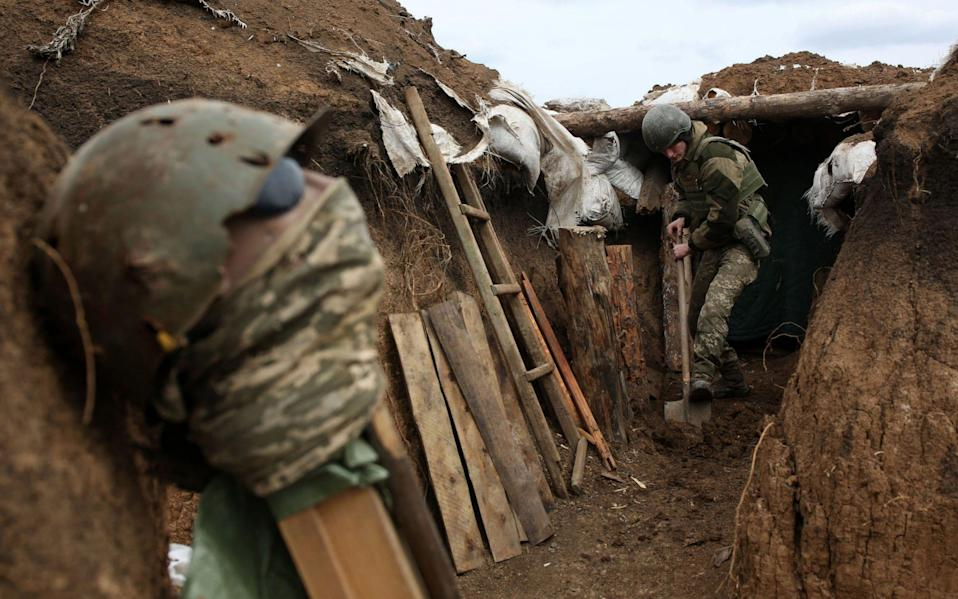 An Ukrainian serviceman digs the ground of a trench as he stands at his post on the frontline on April 8 - AFP