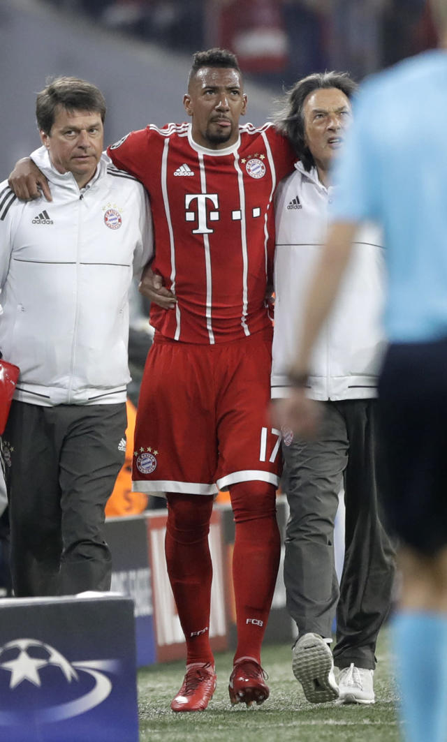 Bayern's Jerome Boateng, center, is lead off the pitch after suffering an injury during the semifinal first leg soccer match between FC Bayern Munich and Real Madrid at the Allianz Arena stadium in Munich, Germany, Wednesday, April 25, 2018. (AP Photo/Matthias Schrader)