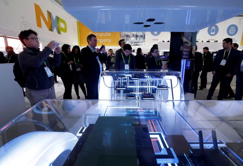 People look over a display in the NXP booth during the 2019 CES in Las Vegas