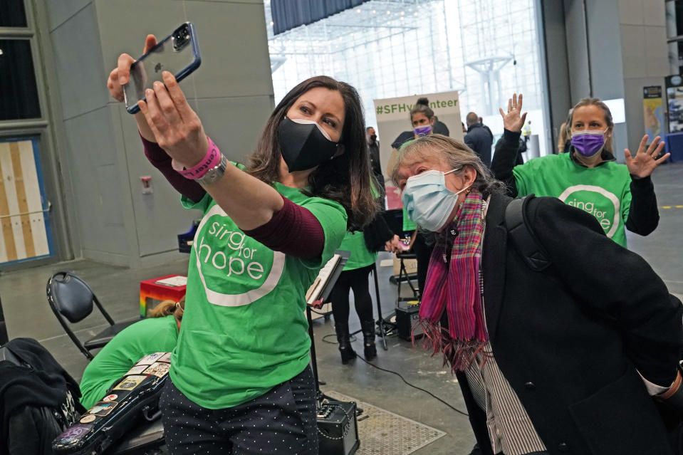 Sing for Hope co-founder Camille Zamora, left, takes a photo with Hildegardt Gemmer, center, and violinist Victoria Paterson, back right, who started her own nonprofit, Music and Medicine, after Gemmer was vaccinated at the Jacob K. Javits Convention Center, Thursday, March 18, 2021, in New York. The center, one of New York City's largest coronavirus vaccination centers is also serving as a home to a series of mini concerts. The music is part of a series of concerts that come from a collaboration between the nonprofit group 'Sing for Hope' and Paterson. (AP Photo/Kathy Willens)