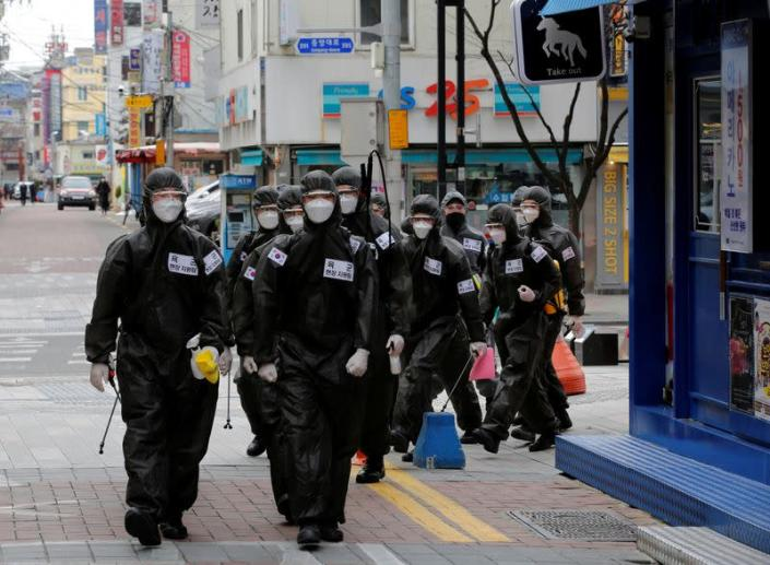 FILE PHOTO: South Korean soldiers in protective gear make their way while they disinfect buildings downtown, following the rise in confirmed cases of coronavirus disease (COVID-19) in Daegu